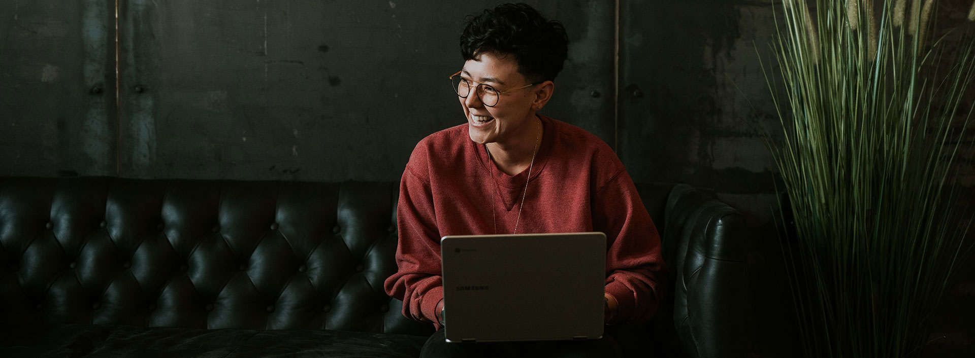 Photo of a worker laughing and working at a computer.