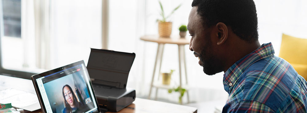 Photo of a man talking to a co-worker on his laptop.