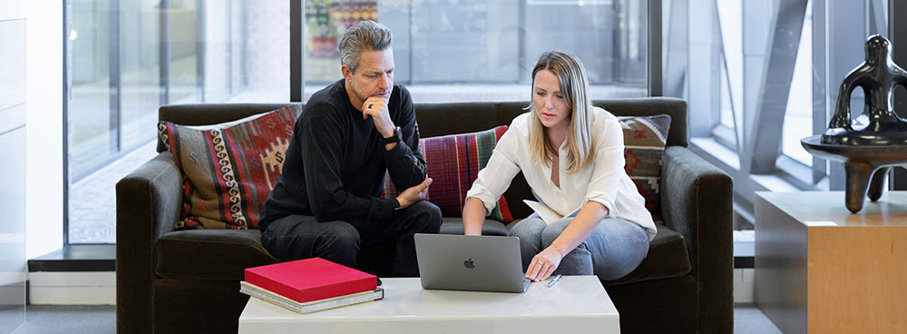Photo of a man and woman working in a casual office setting in from of a laptop.