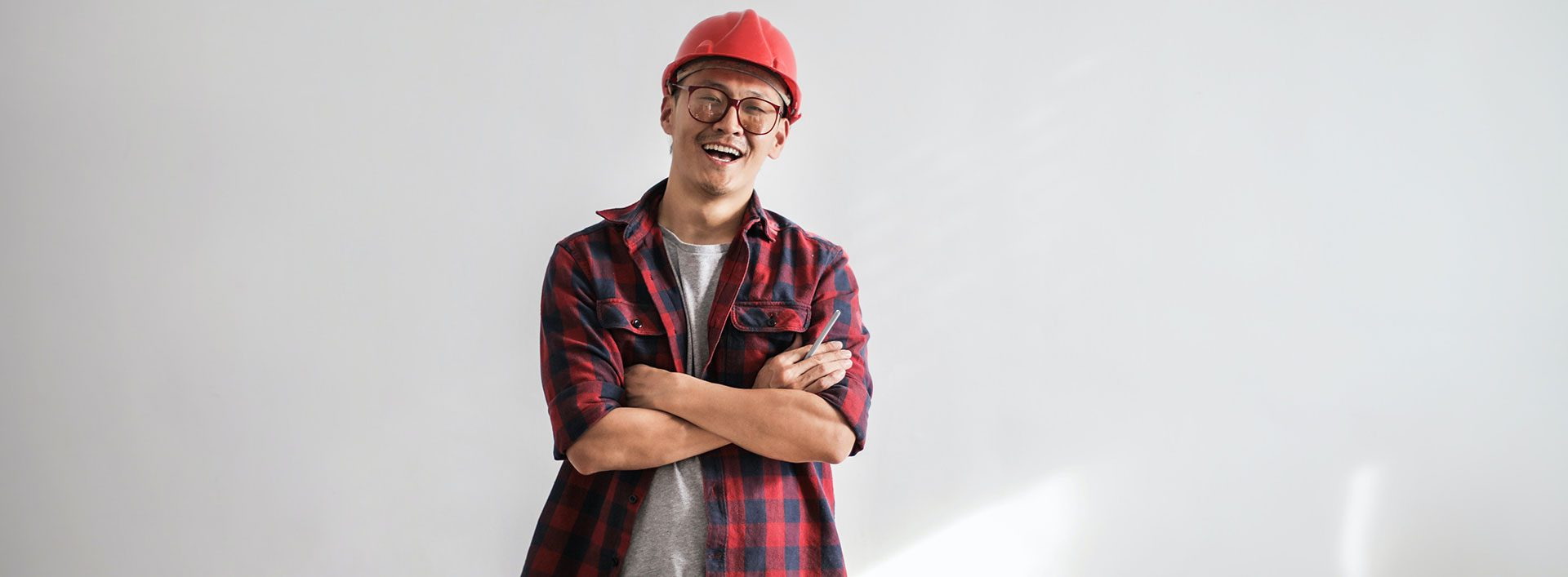 Photo of young man in hard hat with arms crossed and smiling