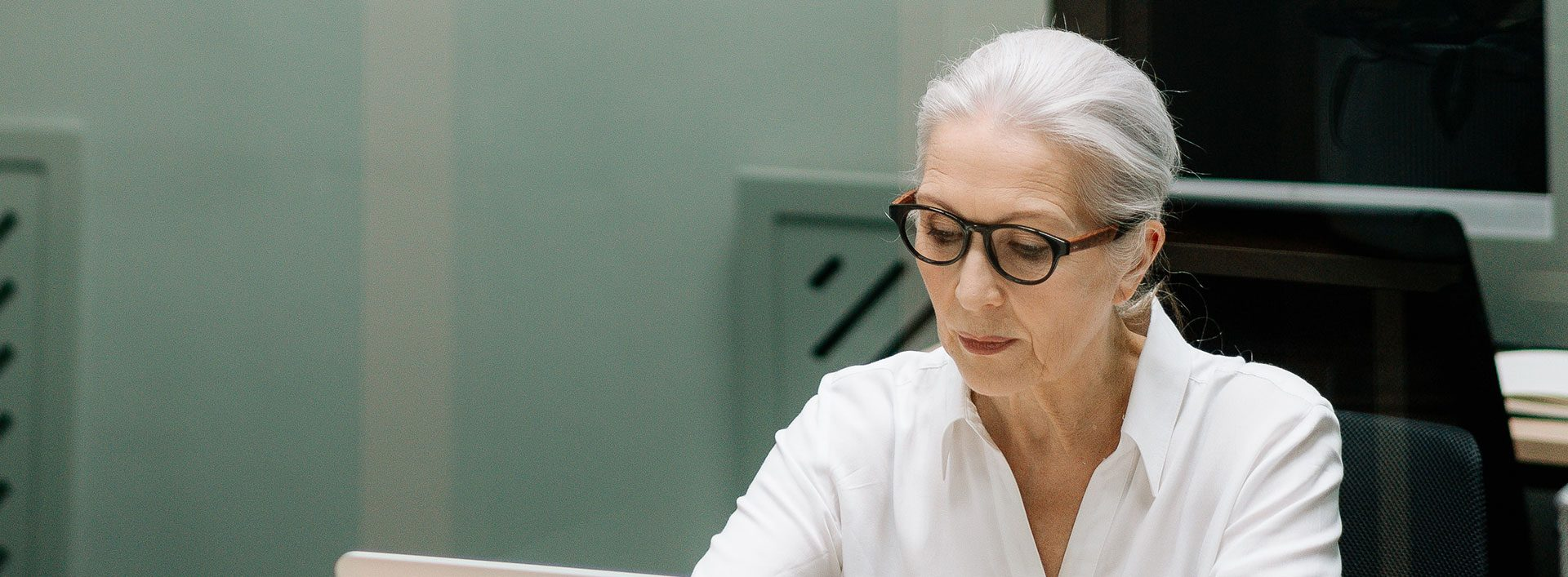 Photo of woman with with white hair and glasses