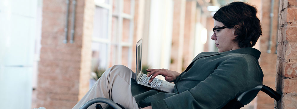 Photo of woman in a wheelchair working on a laptop