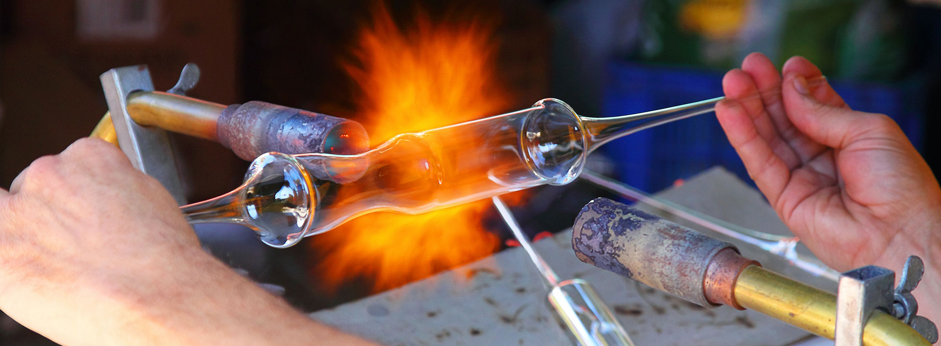 Photo of a worker blowing glass.