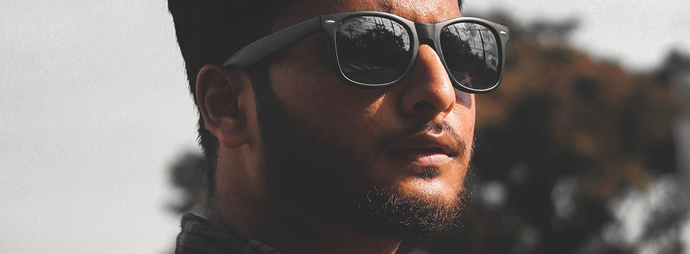Photo of a man with a beard and moustache wearing reflective sunglasses.