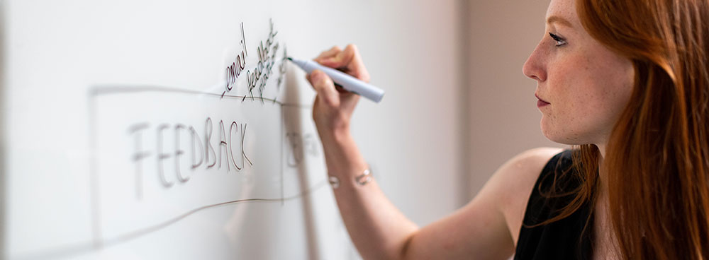Woman writing on a whiteboard during a business seminar.