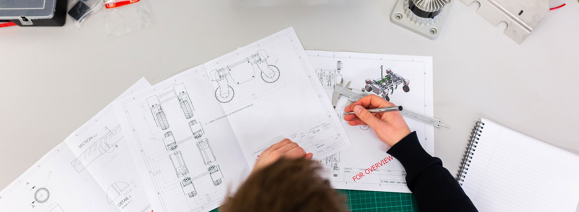 Overhead photo of an engineer reviewing industrial drawings