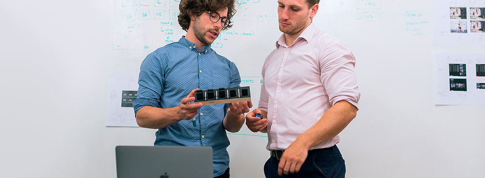 Photo of co-workers examining a product.
