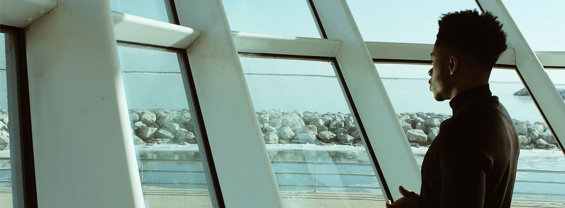 Photo of a man looking out space age looking windows.